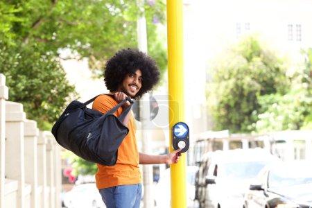 Young guy pushing button to cross street