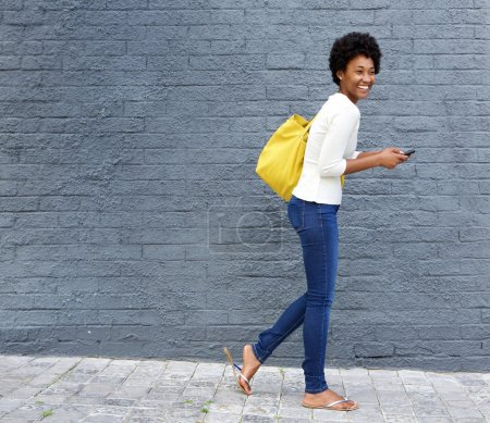 Photo for Full length portrait of a cheerful young african woman walking on street with a mobile phone - Royalty Free Image