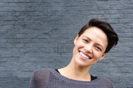 Photo pour Gros plan portrait d'une jeune femme souriante aux cheveux courts sur fond gris - image libre de droit