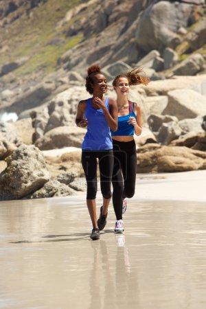 Photo pour Pleine longueur jeunes femmes appréciant courir sur la plage - image libre de droit