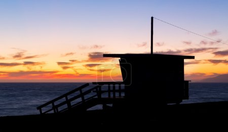 Lifeguard stand at dusk in silhouette at Zuma Beac...