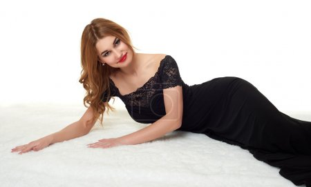 Photo for Beautiful girl lying on fur, dressed in black gown. - Royalty Free Image