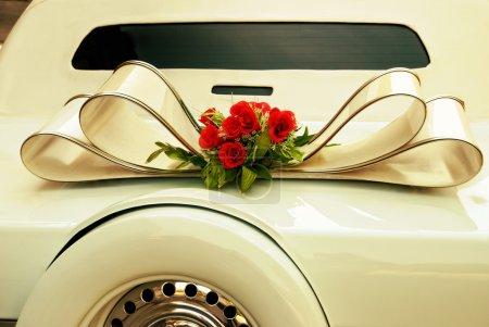Limousine backside ornate with flowers. White wedding retro car closeup. Yellow toned.