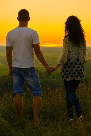 Photo pour Young couple at sunset on sky background, love concept, romantic people - image libre de droit