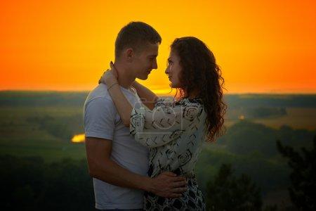 Photo pour Couple romantique au coucher du soleil sur fond de ciel jaune lumineux, notion de tendresse amour, jeunes adultes - image libre de droit