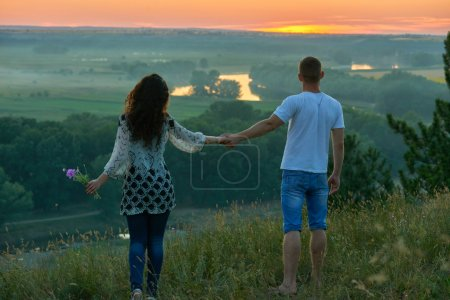 romantic couple walk on hill at sunset on country outdoor, girl with bouquet of wild flower, beautiful landscape and bright yellow sky, love tenderness concept, young adult people