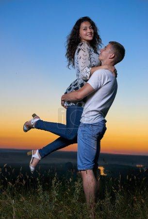 Photo pour Étreinte du couple romantique au coucher du soleil, petit ami suscite une petite amie, beau paysage et ciel jaune lumineux, notion de tendresse amour, jeunes adultes - image libre de droit