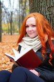 girl with book sit on yellow leaves in autumn forest