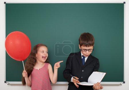 Photo pour Garçon et fille près de la commission scolaire - image libre de droit
