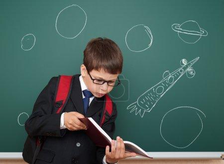 school boy drawing space rocket on board