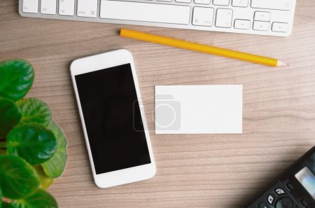 Office desktop with smartphone, computer and blank business card, top view