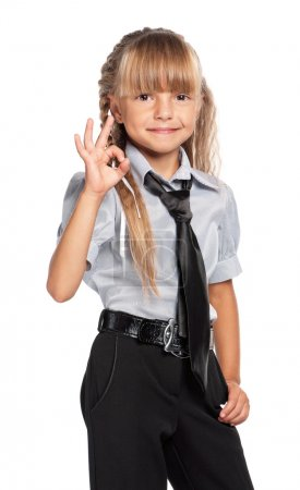 Photo for Happy little girl in school uniform showing ok sign, isolated on white background - Royalty Free Image