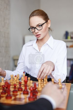 Sexy ceo playing chess with business partner