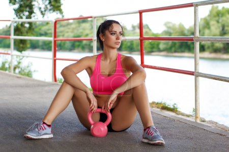Attractive female sitting and resting after workout