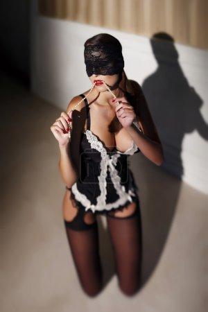 Sensual woman in underwear bite pearls at night