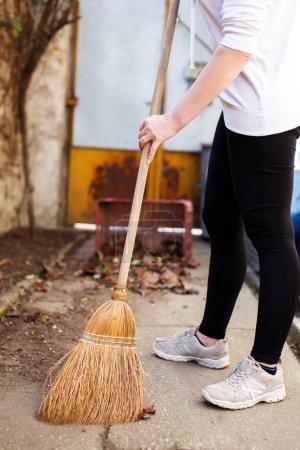 Woman sweeping on backyard