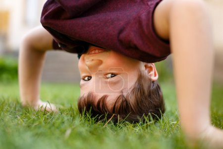 Little boy headstand in grass and laughing