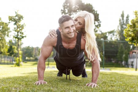 Fit man doing push-ups with woman on back