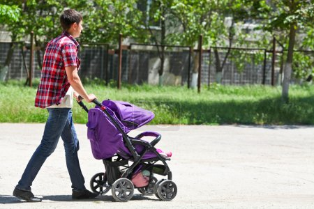 The young father walks with a baby carriage in park