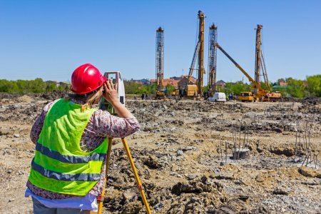 Female geodesist is working with total station on a building sit