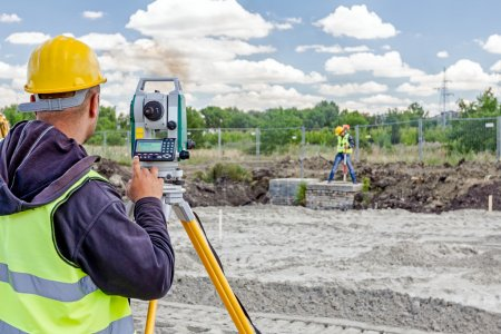 Geodesist is working with total station on a building site. Civi