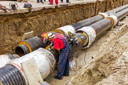 Photo pour Métallurgiste meule soudure sur le nouveau système de chauffage par pipeline . - image libre de droit