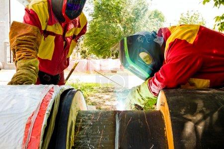 Photo pour Soudeur travaillant sur un pipeline dans un chantier de construction portant un équipement global et de sécurité - image libre de droit