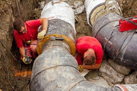 Photo pour Les métallurgistes broient la première soudure sur un nouveau pipeline . - image libre de droit