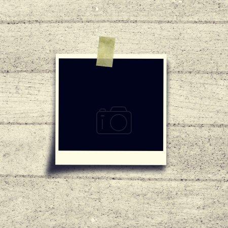 Black photo frame polaroid on cork board background