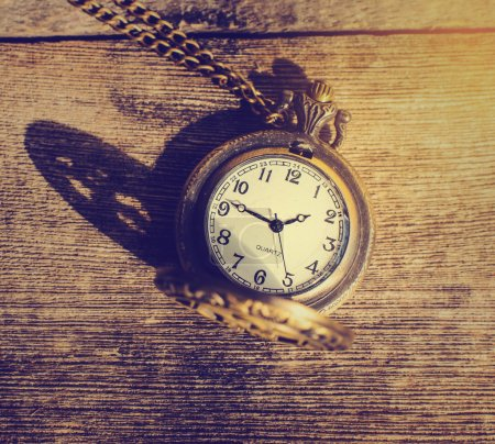 Pocket watch on a wood background with natural light.