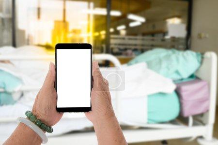Senior hands holding smart phone with blurry hospital room backg