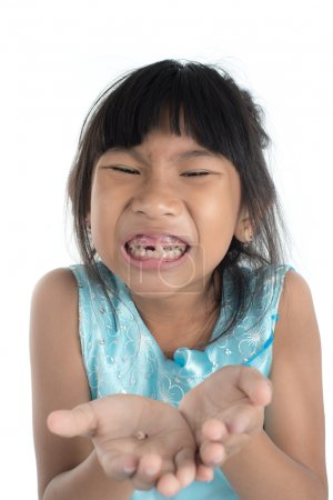 6 years old child has lost the baby tooth. The girl is holding t