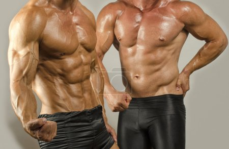 Fit body versus fat body, flexing muscles. Two men showing their biceps,abs, chest and shoulders in a contest