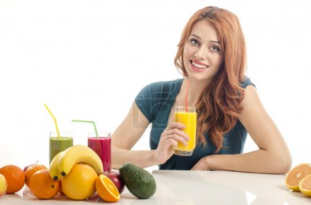 Happy woman having a table full of organic food,juices and smoothie. Cheerful young woman eating healthy salad and fruits. Isolated on white.