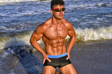 Strong bodybuilder with six pack.Fitness trainer with perfect abs, shoulders,biceps, triceps,chest, flexing his muscles on the beach with sea waves on the background, training in vacation