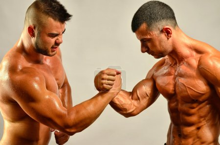 Strong bodybuilders testing their biceps in a skandemberg contes