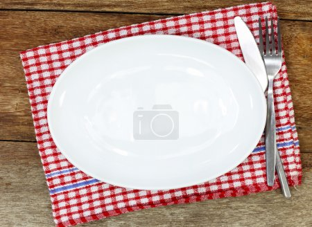 Empty plate, silverware and towel over wooden table background.