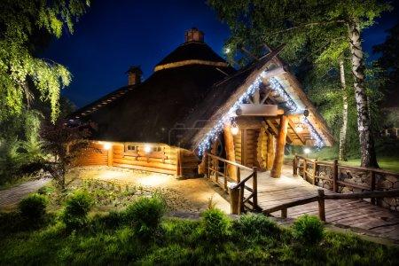 Photo pour Conte de fées maison en bois éclairé lumières sous le ciel nocturne - image libre de droit