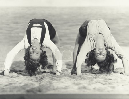 women doing backbends on the beach