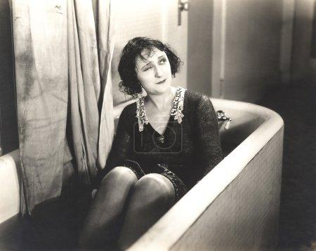 Winking woman in bathtub fully clothed  (OLVI007_O...