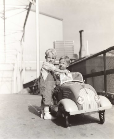 Foto de ¿Puedo darle un ascensor? dos chicos lindos jugando con coches de juguete - Imagen libre de derechos