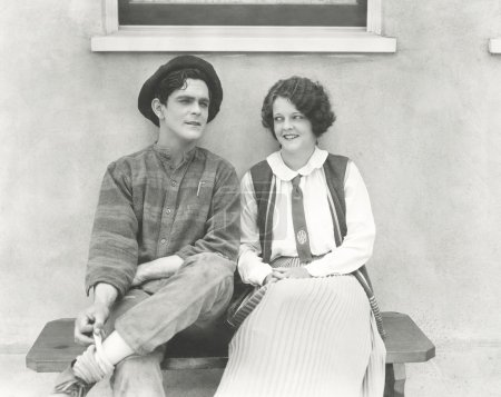 Young man and woman sitting outdoors