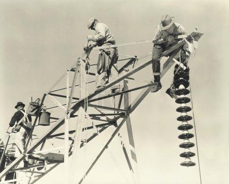 Photo pour Trois hommes qui travaillaient sur les lignes électriques - image libre de droit