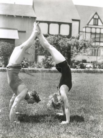ouple doing handstands in yard