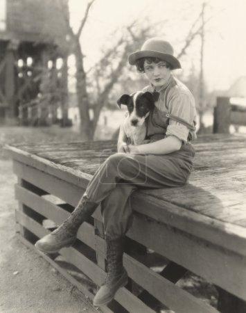 Foto de Joven mujer sentada al aire libre con su perro - Imagen libre de derechos
