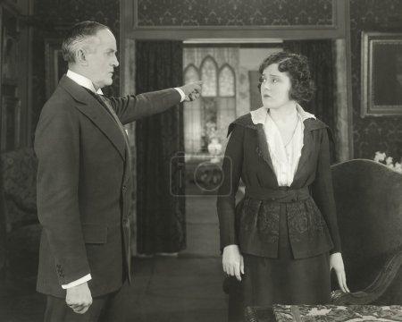 man showing woman the door