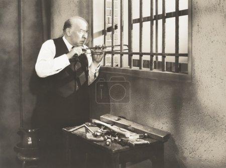 Man sawing through bars