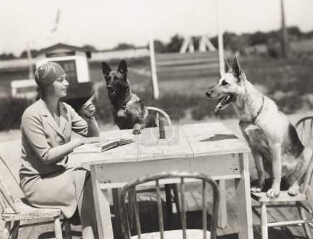 woman sitting at table with dogs