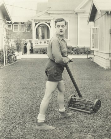 man  with a push reel lawn mower