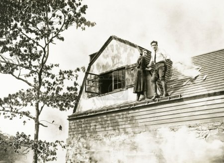 man and woman standing on roof